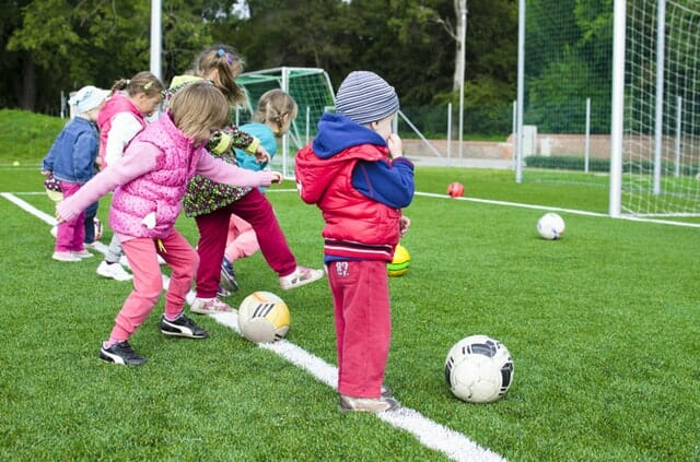 budget beating ideas | kids playing football on a large AstroTurf field