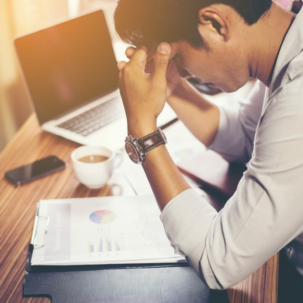 a man with black hair sat with his elbows at his desk worrying about his financial stress